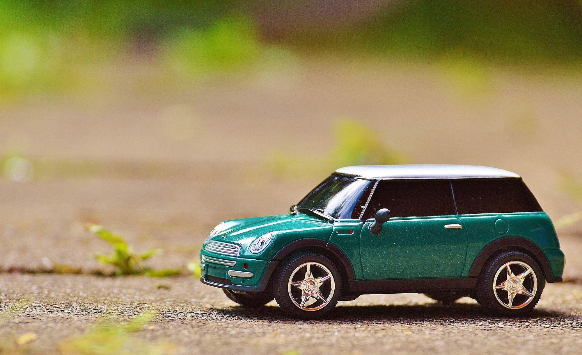 miniature car on concrete with plants showing between the gaps