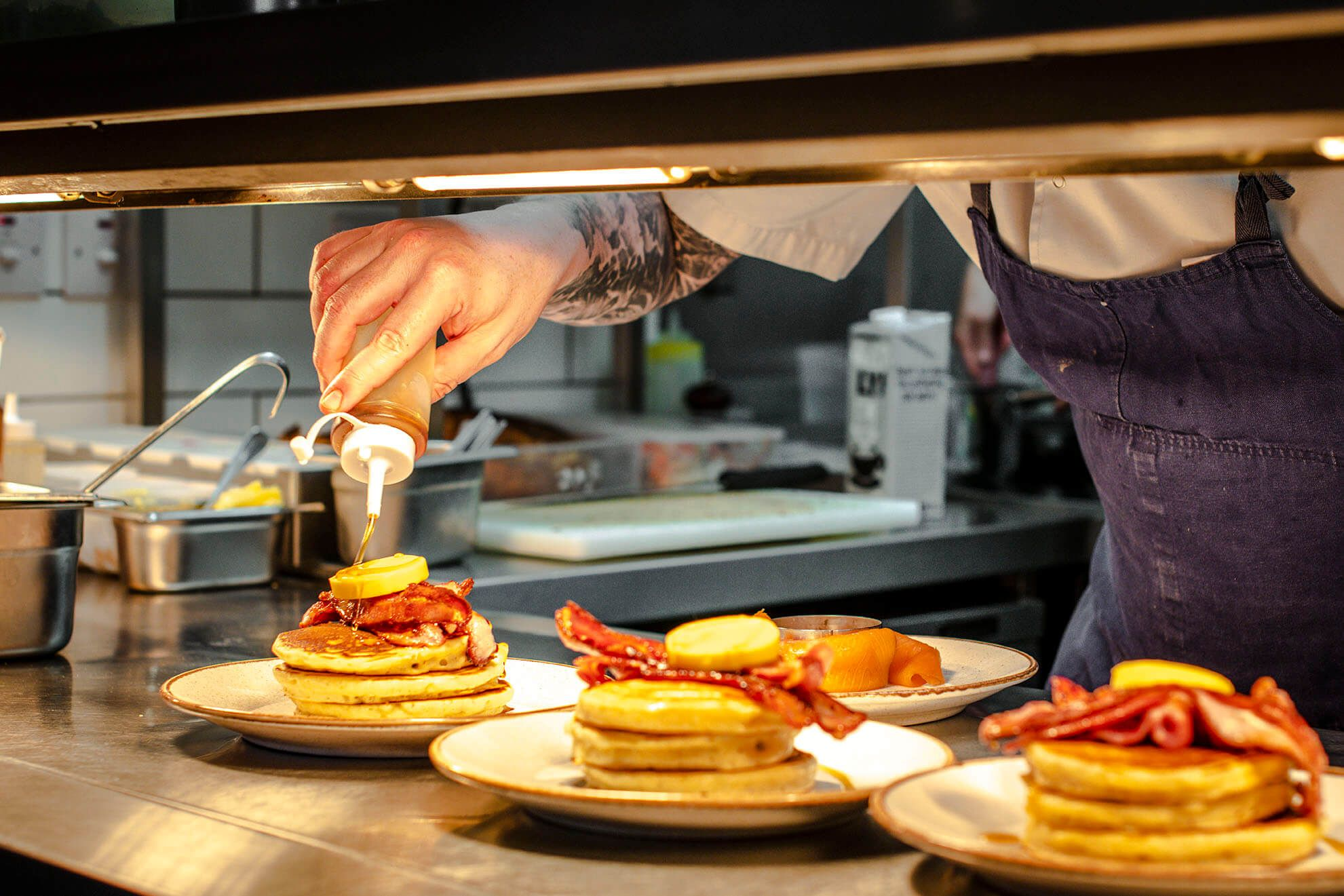 Pancakes and bacon being prepared in by chef in cafe kitchen.